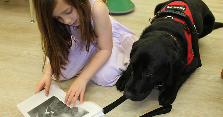 Young girl reading with a service dog